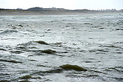 The Hague, South-Holland/Netherlands - 200226: Wild sea with waves on a stormy day with dunes and houses on the background