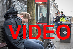 VIDEO AVAILABLE HERE: https://we.tl/4As1auVP06<br /> <br /> © Licensed to London News Pictures . 06/04/2017 . Manchester , UK . A paramedic tends to a man , believed to have consumed spice , in Piccadilly Gardens , as another man consumes a rolled cigarette believed to contain spice , in an adjacent telephone box and a third man lies slumped on a bench . An epidemic of abuse of the drug spice by some of Manchester's homeless population , in plain sight , is causing users to experience psychosis and a zombie-like state and is daily being witnessed in the Piccadilly Gardens area of Manchester , drawing large resource from paramedic services in the city centre . Photo credit : Joel Goodman/LNP