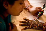 A young Indian bride lies on her bed as she has henna decorated onto her  arm and palm by a local artist, as she begins preparations  for her wedding ceremony, Jaipur, India