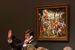 "© Licensed to London News Pictures. 07/12/2016. London, UK. Sotheby's staff make bids on behalf of telephone clients in front of ""Return from Kermesse"" by Pieter Brueghel the Younger which sold for a hammer price of GBP2.15m (est GBP 2-3m) at the Old Masters Evening Sale at Sotheby's in New Bond Street. Photo credit : Stephen Chung/LNP"
