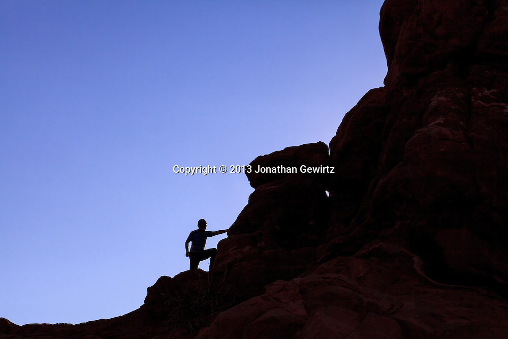 A visitor on Balanced Rock in Arches National Park, Utah. WATERMARKS WILL NOT APPEAR ON PRINTS OR LICENSED IMAGES.