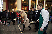 Shrove Tuesday festivities as competitors line up for the Leadenhall Market Pancake Day Race on 13th February 2018 in London, United Kingdom. Competing teams of City workers outside The Lamb Tavern tackle the 25m course, competing to win the coveted frying pan trophy as they flip their way around the historic 14th century market.