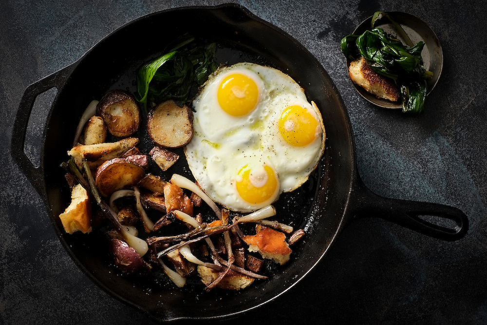 Fried eggs with ramps, bacon and potatoes in a cast iron skillet on dark background.