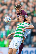 Jimmy Dunne (#3) of Heart of Midlothian jumps over Kristoffer Ajer(#35) of Celtic FC during the Betfred League Cup semi-final match between Heart of Midlothian FC and Celtic FC at the BT Murrayfield Stadium, Edinburgh, Scotland on 28 October 2018.
