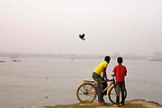 Two boys, one with a bicycle, watch the river Karnaphuli from the southern bank. Chittagong, Bangladesh