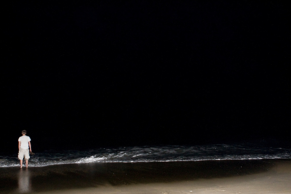 A lone male figure lets the waves roll over his feet at nighttime while the shocking flash of the camera captures the scene.