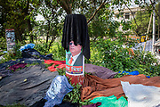 Textiles drying on a pillar with a political poster on it  in a community living next to the garment industries.<br /> Environmental pollution on the river banks surrounding some of the textile industry buildings of Savar Upazila, a district of Dhaka, Bangladesh.  30th September 2018. The garment business is the main industry of Savar Upazila, a district in the northern part of Dhaka.  (photo by Andrew Aitchison / In pictures via Getty Images)
