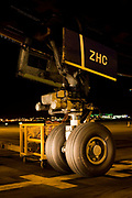 "The giant nosewheel of a Boeing 747-400 airliner is parked on the apron area during its overnight turnround at Heathrow Airport. The engineering of this magnificent piece of aviation design is highlighted by the headlights of an airfield vehicle and the tyres sit firmly on the tarmac at an exact parking spot according to the aircraft's length in order for it to be met by air bridges and service trucks. The nose wheel is used for steering the jet when on the ground. From writer Alain de Botton's book project ""A Week at the Airport: A Heathrow Diary"" (2009)."