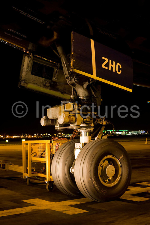 """The giant nosewheel of a Boeing 747-400 airliner is parked on the apron area during its overnight turnround at Heathrow Airport. The engineering of this magnificent piece of aviation design is highlighted by the headlights of an airfield vehicle and the tyres sit firmly on the tarmac at an exact parking spot according to the aircraft's length in order for it to be met by air bridges and service trucks. The nose wheel is used for steering the jet when on the ground. From writer Alain de Botton's book project """"A Week at the Airport: A Heathrow Diary"""" (2009)."""