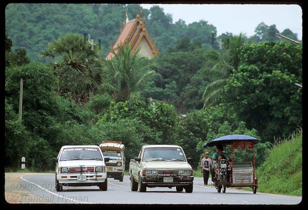 Cars and motorcycle-van zip along highway past Buddhist shrine on Phuket Island. Thailand