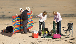 © Licensed to London News Pictures. 28/03/2012..Saltburn, England..As temperatures rise this week the beach at Saltburn in Cleveland attracts the visitors as they enjoy the warm weather. First priority is to get the windbreak up...Photo credit : Ian Forsyth/LNP