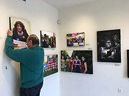 """Huntington, New York USA. March 27, 2017. After end of """"Her Story Through Art"""" Invitational Exhibition celebrating Women's History Month, artwork is taken down at Main Street Gallery at Huntington Arts Council. Bob Stuhmer helps remove photographs by Ann Parry."""
