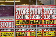 'Store Closing, All Stock Reduced' posters stuck to the window of a Woolworths shop in the town of Nailsea, Nth Somerset. .