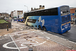 © Licensed to London News Pictures. 27/11/2016. London, UK. A French tourist coach sits stranded after it fell into a sinkhole on Lee High Road in Lewisham. The road has been closed off and police declared a 'major incident' after a French tourist coach with 100 passengers on board fell into a sinkhole caused by a burst water mains, flooding a long stretch of the road including many local businesses. Photo credit: Rob Pinney/LNP