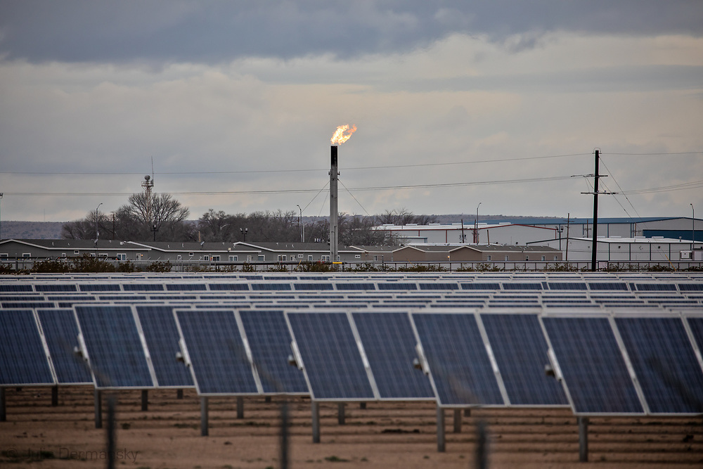 Flare at and oil and gas industry site in the Permian Basin next to a solar farm just outside of Carslbad New Mexico