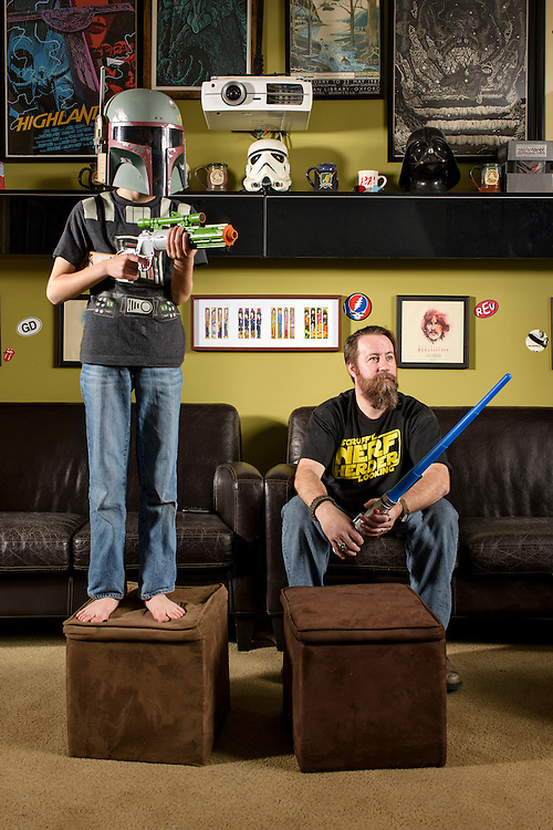 Hyattsville, Maryland - November 01, 2015: Chris Giunta and his nine-year-old son Dominic Giunta pose for a portrait in their home theater, which is heavily decorated with the original Star Wars trilogy memorabilia.<br /> <br /> <br /> Chris Giunta, from Hyattsville, Md., is a Star Wars fanatic who hates Episode 1-3. He moved to San Fransisco from Maryland and camped out for a month to be one of the first in line to see The Phantom Menace. He even proposed to his wife before the movie started. These days he forbids his children from watching the first three films and the re-released digitally enhanced versions of the original trilogy. He hopes the new films live up to his expectations. <br /> <br /> <br /> CREDIT: Matt Roth for The Wall Street Journal