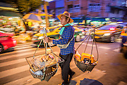 19 OCTOBER 2012 - BANGKOK, THAILAND:   A food vendor carries his yoke through the Bangkok Flower Market. He sells eggs he grills on a charcoal grill right in the basket on the front of the yoke. The Bangkok Flower Market (Pak Klong Talad) is the biggest wholesale and retail fresh flower market in Bangkok.  The market is busiest between 3:30AM and 6AM. Thais grow and use a lot of flowers. Some, like marigolds and lotus, are used for religious purposes. Others are purely ornamental.          PHOTO BY JACK KURTZ