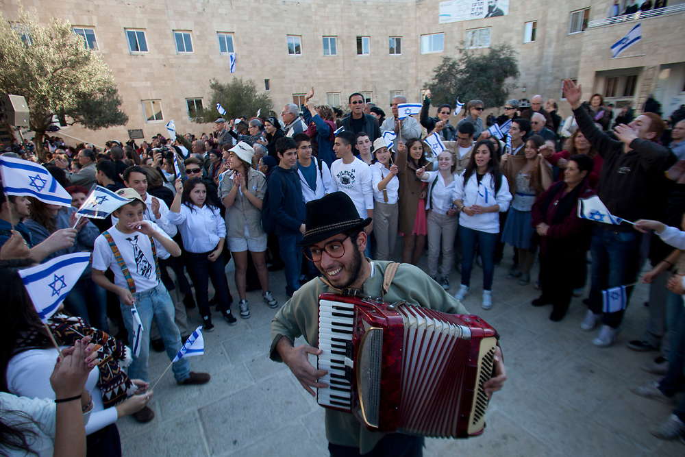 Israelis wave flags and celebrate in Jerusalem, on November 29, 2011, as they participate in a historical reenactment of the celebrations that took place 64 years ago, on November 29, 1947, after the United Nations General Assembly adopted the partition plan for Palestine, which led to the establishment of the state of Israel.
