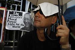 July 13, 2017 - Hong Kong, CHINA - A pro-democracy protester cover his head with towel under the summer heat outside Liaison Office of the Peoples Government in the HKSAR, staging sit-in for Chinese dissident, political prisoner and Nobel Peace Prize Laureate LIU XIAO BO demanding Lius immediate release.July 13, 2017.Hong Kong.ZUMA/Liau Chung Ren (Credit Image: © Liau Chung Ren via ZUMA Wire)