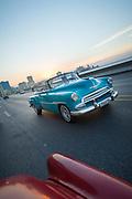 Vintage cars driving along Malecon road at sunset, Havana, Cuba