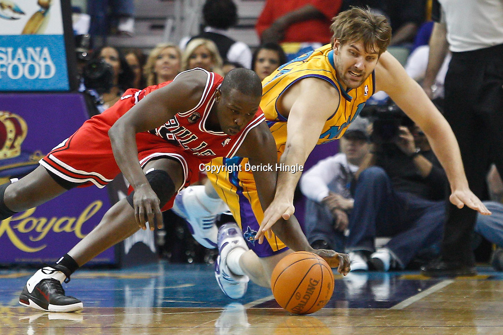 February 12, 2011; New Orleans, LA, USA; New Orleans Hornets center Aaron Gray (34) and Chicago Bulls small forward Luol Deng (9) scramble for a loose ball during the first quarter at the New Orleans Arena.   Mandatory Credit: Derick E. Hingle
