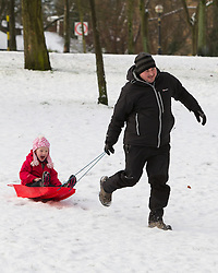 © Licensed to London News Pictures . 26/01/2013 . Salford , UK . A smiling girl on a sled is pulled along in the fresh snow . People enjoy fresh overnight snow this morning (26th January 2013) in Buile Hill Park , Salford . Photo credit : Joel Goodman/LNP