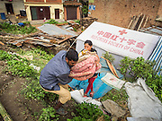 02 AUGUST 2015 - BHAKTAPUR, NEPAL:  People gather their bedding in a small Internal Displaced Person (IDP) camp at Durbar Square in Bhaktapur for people left homeless by the Nepal earthquake. The Nepal Earthquake on April 25, 2015, (also known as the Gorkha earthquake) killed more than 9,000 people and injured more than 23,000. It had a magnitude of 7.8. The epicenter was east of the district of Lamjung, and its hypocenter was at a depth of approximately 15 km (9.3 mi). It was the worst natural disaster to strike Nepal since the 1934 Nepal–Bihar earthquake. The earthquake triggered an avalanche on Mount Everest, killing at least 19. The earthquake also set off an avalanche in the Langtang valley, where 250 people were reported missing. Hundreds of thousands of people were made homeless with entire villages flattened across many districts of the country. Centuries-old buildings were destroyed at UNESCO World Heritage sites in the Kathmandu Valley, including some at the Kathmandu Durbar Square, the Patan Durbar Squar, the Bhaktapur Durbar Square, the Changu Narayan Temple and the Swayambhunath Stupa. Geophysicists and other experts had warned for decades that Nepal was vulnerable to a deadly earthquake, particularly because of its geology, urbanization, and architecture.      PHOTO BY JACK KURTZ