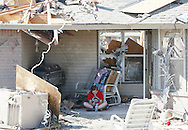 A woman sits on the back patio of her tornado-destroyed home next to Briarwood elementary school in Oklahoma City, Oklahoma May 22, 2013.  Rescue workers with sniffer dogs picked through the ruins on Wednesday to ensure no survivors remained buried after a deadly tornado left thousands homeless and trying to salvage what was left of their belongings. Curvature of horizon in the photo is due to an ultra-wide angle lens.  REUTERS/Rick Wilking (UNITED STATES)