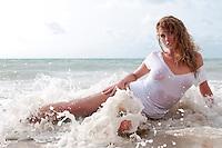Sensual woman posing in the ocean wet.