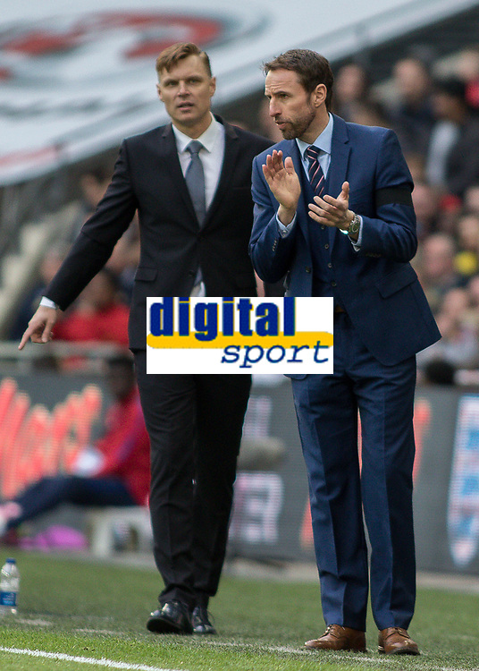 Football - 2016 / 2017 World Cup Qualifier - UEFA Group F: England vs. Lithuania<br /> <br /> England Manager Gareth Southgate with Lithuania Head Coach Edgaras Jankauskas in the background at Wembley.<br /> <br /> COLORSPORT/DANIEL BEARHAM