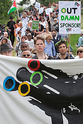 © licensed to London News Pictures. London, UK 28/07/2012. Protester posing with banners and placards as anti-Olympics protesters marching from Mile End Park to Victoria Park in order to protest against the greed of the Olympic sponsors. Photo credit: Tolga Akmen/LNP