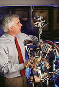 Micro Technology: Steve Jacobsen, at the University of Utah's micromechanics laboratory with the undressed frame of a Disneyland robot. He is holding a silicon wafer in his left hand; This contains many micro motors and micro-actuators that could soon revolutionize robot design. Micromechanic devices, like silicon microcircuits, operate with static electrical charges, and so would require only one power cable, replacing the 200 that he is holding in his right hand. Model Released [1990]