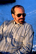 Man age 42 relaxing in sun on ski trip vacation at Big Powderhorn Mountain.  Bessemer  Michigan USA