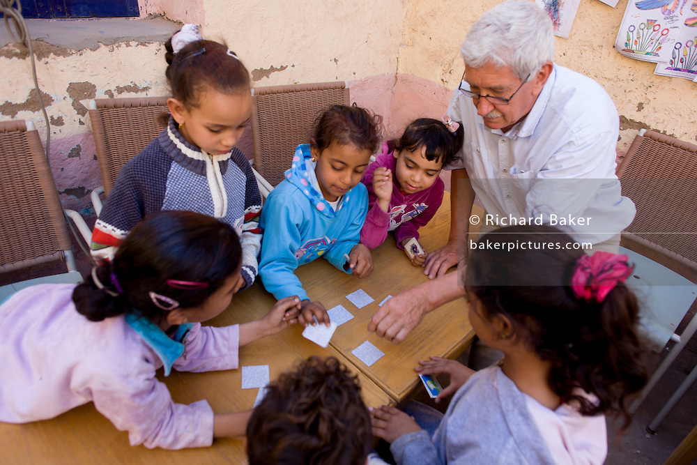Local children get help with memory card games from a Belgian teaching volunteer at the American-sponsored Theban Mapping Project Library on the West Bank of Luxor, Nile Valley, Egypt. The Theban Mapping Project's goal is to enable local people to have a place where they can read and learn. The organisation is run by American Egyptologist Dr Kent Weeks who is committed to the original goal of accurately documenting the archaeological heritage of Thebes