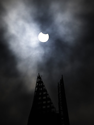 © Licensed to London News Pictures. 10/06/2021. London, UK. The moon passes in front of the sun during a partial eclipse viewed in central London at The Shard. Photo credit: Peter Macdiarmid/LNP