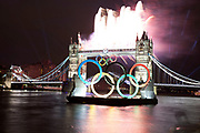 London, UK. Friday 27th July 2012. Olympic flame passes Tower Bridge with fireworks on way to the opening ceremony. London's greatest landmark bridge lights up as the Olympic torch passes by in a high speed boat.