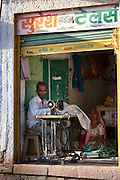 Indian man and wife sewing fabric in village of Rohet in Rajasthan, Northern India