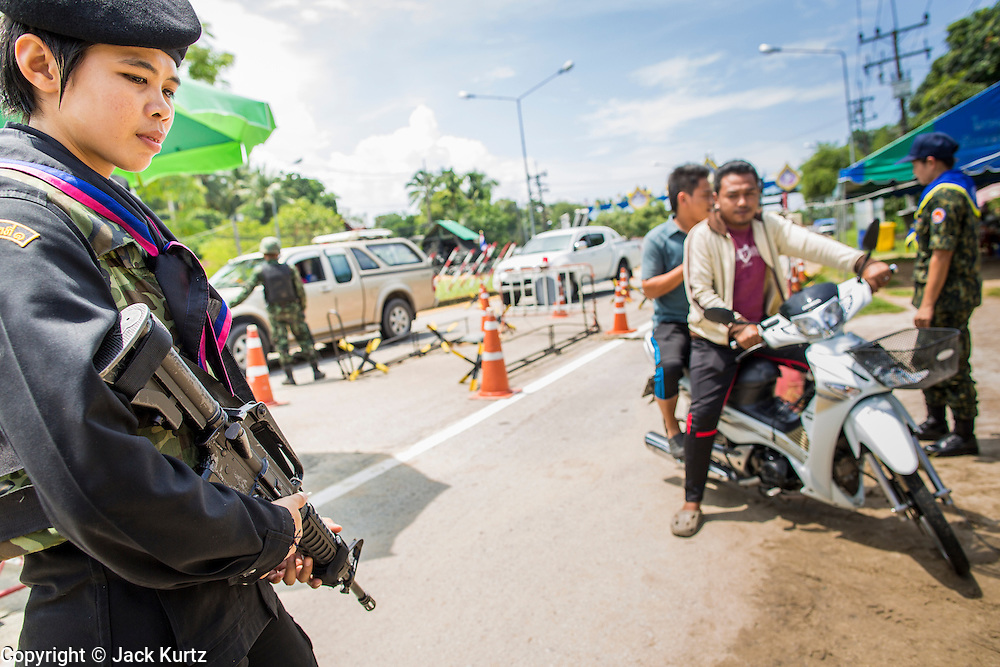 """25 OCTOBER 2012 - TAK BAI, NARATHIWAT, THAILAND: AThai woman Ranger (paramilitary operating under Army command) at a checkpoint in Tak Bai, Thailand. The """"Tak Bai Incident"""" took place on Oct. 25 in Tak Bai, Narathiwat, Thailand during the Muslim insurgency in southern Thailand. On that day, a crowd gathered to protest the arrest of local residents. Police made hundreds of arrests during the protest and transported the arrested to Pattani, about two hours away, in another province. They were transported in locked trucks and more than 80 people suffocated en route. This enraged local Muslims and shocked people across Thailand. No one in the Thai army accepted responsibility for the deaths and no one was ever charged. In the past, the anniversary of the incident was marked by protests and bombings. This year it was quiet. More than 5,000 people have been killed and over 9,000 hurt in more than 11,000 incidents, or about 3.5 a day, in Thailand's three southernmost provinces and four districts of Songkhla since the insurgent violence erupted in January 2004, according to Deep South Watch, an independent research organization that monitors violence in Thailand's deep south region that borders Malaysia.   PHOTO BY JACK KURTZ"""