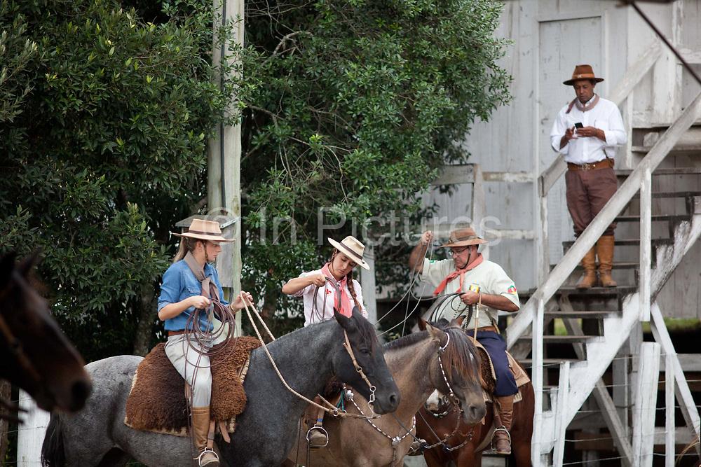 Young Brazilian Gauchas cowgirls females, riding horses, preparing to compete in a rodeo. Gaucho cowboy Rodeo, Flores de Cunha, Rio Grande do Sul.