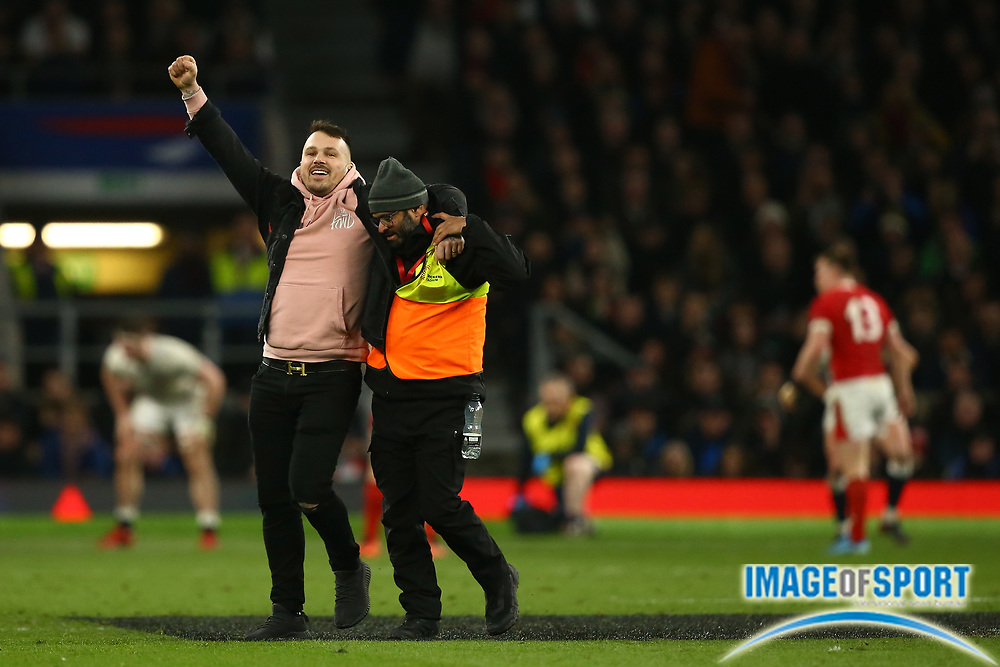A pitch invader is removed by a steward during the Guinness Six Nations between England and Wales at Twickenham Stadium, Saturday, March 7, 2020, in London, United Kingdom. (Mitchell Gunn-ESPA-Images/Image of Sport)