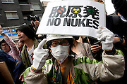 People taking part in The Hangenbatsu Choukyodai Demo which translates at the Anti Nuclear powerplants super huge demo protest against the use of nuclear power. The subject of the dangers of nuclear power generation has become more pressing and popular since the March 11th 2011 earthquake and tsunami damaged the Fukushima Daichi nuclear power plant 200 kms north of Tokyo causing radioactive leaks and bringing the spectre of nuclear contamination to the capital. Organizers said around 7,000 people turned up for the demo that started in Koenji Chou Park and marched around Koenji with punk bands bands leading the good-natured protest as they preformed on a truck at the head of the march. Tokyo, Japan Sunday April 10th 2011