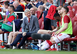 Arsenal manager Arsene Wenger (left) and assistant Steve Bould chat with Arsenal's Per Mertesacker, Ainsley Maitland-Niles and Aaron Ramsey (right) during the Premier League match at the Emirates Stadium, London.