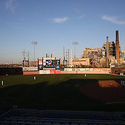 The Bridgeport Harbor Power Station provides a back drop to the ballpark as players stand for the National anthem during the Bridgeport Bluefish V Southern Maryland Blue Crabs, Atlantic League, Minor League ballgame at Harbor Yard Ballpark, Bridgeport, Connecticut, USA. Photo Tim Clayton