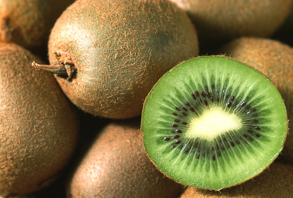 Close up selective focus photo of a group of Kiwis with one cut in half to show the beautiful fruit