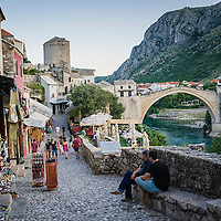 MOSTAR, BOSNIA AND HERZEGOVINA - JUNE 26:  Tourists walk along the street leading to the Old Bridge on  June 26, 2013 in Mostar, Bosnia and Herzegovina.The Siege of Mostar reached its peak and more cruent time during 1993. Initially, it involved the Croatian Defence Council (HVO) and the 4th Corps of the ARBiH fighting against the Yugoslav People's Army (JNA) later Croats and Muslim Bosnian began to fight amongst each other, it ended with Bosnia and Herzegovina declaring independence from Yugoslavia.  (Photo by Marco Secchi/Getty Images)