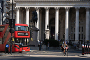 A London bus follows a male cyclist across the new layout opposite Royal Exchange at Bank junction which has recently been altered to stop cars driving past the Bank of England during the Coronavirus pandemic - a time when office workers are still largely working from home, on 16th September 2020, in London, England.