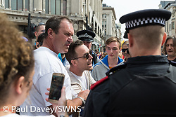 """One of the demonstration's organisers argues with a police officer as several hundred protesters in London in central London demand the release of """"political prisoner"""" right wing talisman Stephen Yaxley-Lennon  - also known as Tommy Robinson, who was imprisoned for contempt of court. London, August 03 2019."""