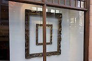 Square shaped picture frames in the window of an art gallery in St James's, central London.