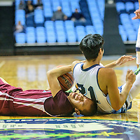 Ganado Hornet Daryl Lincoln (14), left, wines after Window Rock Scout Koeby Emerson (21) rolls over him during the Tournament of Champions at the Window Rock Scout Event Center in Fort Defiance Wednesday