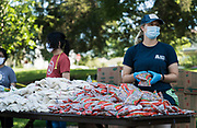 A volunteer distributes bags of dried beans to local residents during a pop up grocery event at Powderhorn Park in Minneapolis, Minnesota, U.S., on Friday, July 24, 2020. Photographer: Ben Brewer/Bloomberg
